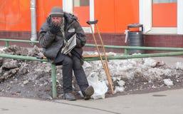 Weißer Obdachloser in Russland, in Moskau am 28. März, eine Zeitung lesend stockfotos