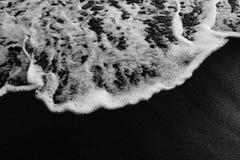Weißer Ozeanschaum auf vulkanischer Beschaffenheit des schwarzen Sandes Lizenzfreie Stockbilder