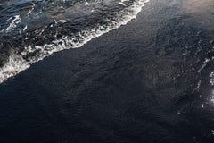 Weißer Ozeanschaum auf vulkanischer Beschaffenheit des schwarzen Sandes Lizenzfreies Stockfoto