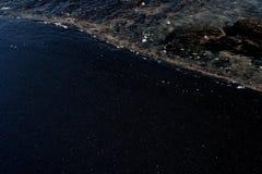Weißer Ozeanschaum auf vulkanischer Beschaffenheit des schwarzen Sandes Stockfotos