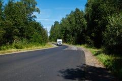 Weißer Packwagen auf der Asphaltstraße Lizenzfreie Stockfotos