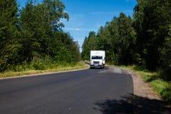 Weißer Packwagen auf der Asphaltstraße Lizenzfreie Stockfotografie