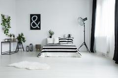 Weißer Pelz auf Boden im minimalistic Schlafzimmer stockbild