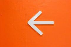 Weißer Pfeil auf orange Wand Stockbild