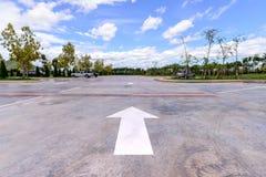 weißer Pfeil auf Parkplatz mit Autohintergrund Stockfotos