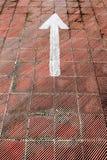 Weißer Pfeil gemalt auf einem Parkboden Stockfotografie
