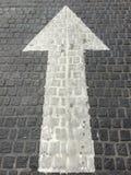 Weißer Pfeil singen auf den Steinziegelsteinen Stockfoto