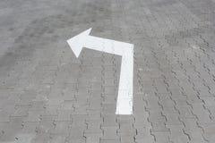 Weißer Pfeil unten auf Straßenfliese Lizenzfreie Stockfotografie