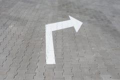 Weißer Pfeil unten auf Straßenfliese Lizenzfreies Stockbild