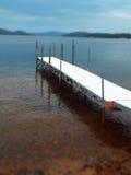 Weißer Pier, der in See mit Weichzeichnungsgebirgshintergrund verlängert stockfotos