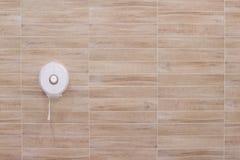 Weißer Plastikgewebekasten, der an den hölzernen Fliesenwandmustern in horizontalem hängt stockfotos