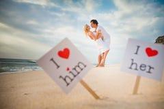 Weißer Rahmen des Liebeskonzeptes mit rotem Herzen und der Paare am Hintergrund Stockfotos