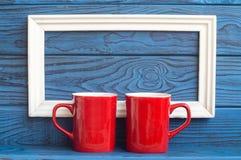 Weißer Rahmen und zwei rote Kaffeetassen auf einem Hintergrund des blauen Ebers Stockbilder