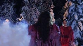 Weißer Rauch bedeckt den Kerl und Mädchen in der roten Kleidung anstarrend entlang einander im Wald stock footage