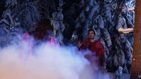 Weißer Rauch bedeckt den Mann und Frau in der roten Kleidung anstarrend entlang einander im Wald stock footage