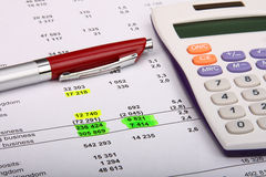 Weißer Rechner und eine Feder auf einem Finanzreport Lizenzfreies Stockfoto