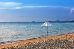 Weißer Regenschirm auf dem Strand stockbilder