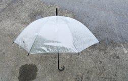 Weißer Regenschirm auf der Straße Lizenzfreies Stockbild