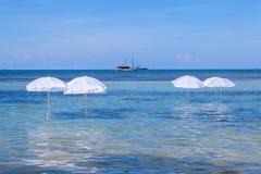 Weißer Regenschirm auf tropischem Strand des Sommers Stockfoto