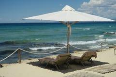 Weißer Regenschirm mit leeren Strandbetten und -tüchern auf Griechenland Stockbilder