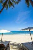 Weißer Regenschirm und Stühle auf weißem Strand Lizenzfreies Stockbild