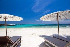 Weißer Regenschirm und Stühle auf weißem Strand Lizenzfreie Stockfotos