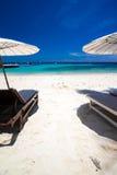 Weißer Regenschirm und Stühle auf weißem Strand Stockfotografie