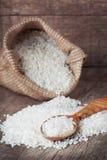 Weißer Reis auf dem hölzernen Löffel und in der Sacktasche Lizenzfreies Stockbild