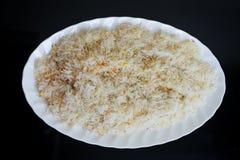 Weißer Reis auf schwarzem Hintergrund Stockbilder