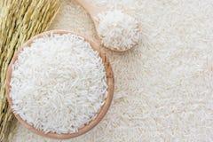 Weißer Reis in der Schüssel und in einer Tasche, ein hölzerner Löffel und Reispflanze auf Hintergrund des weißen Reises Lizenzfreies Stockbild