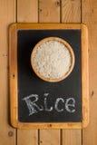 Weißer Reis in einer hölzernen Schüssel auf einer Tafel mit den Wörtern Lizenzfreie Stockfotografie