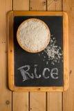 Weißer Reis in einer hölzernen Schüssel auf einer Tafel mit den Wörtern Lizenzfreie Stockbilder