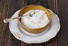 Weißer Reis in einer keramischen Schüssel auf rustikalem hölzernem Hintergrund Stockbild
