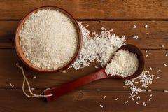 Weißer Reis in einer keramischen Schüssel und in einem Löffel auf einem Holztisch Stockfotografie