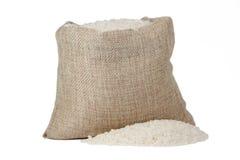 Weißer Reis im Leinwandsack lokalisiert auf weißem Hintergrund Stockfotos