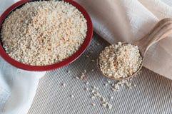 Weißer Samen des indischen Sesams auf hölzernem Löffel und Platte Stockfotografie