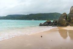 Weißer Sand, bewölkte Himmel, Granitsteine und Türkismeer am Märchenland setzen, Seychellen Afrika auf den Strand stockfotografie
