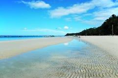 Weißer Sand-Strand mit dem Himmel reflektiert im Wasser Lizenzfreies Stockbild