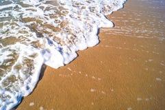 Weißer Schaum bewegt auf den Seestrand von Thailand wellenartig Lizenzfreie Stockfotos