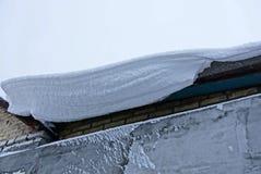 Weißer Schneeantrieb auf dem Dach des Hauses Lizenzfreie Stockbilder