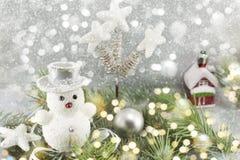Weißer Schneemann unter verzierten Tannenzweigen Lizenzfreie Stockbilder