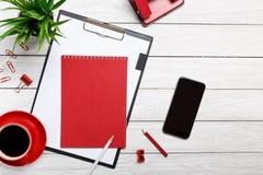 Weißer Schreibtisch verschalt Notizblockschalenmorgenkaffeeuhrbüroklammer-Arbeitsflusssitzung des Ordners rote stockfotografie