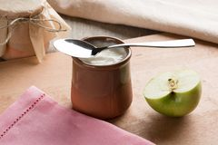 Weißer selbst gemachter Jogurt in einem Lehmglas mit einem Apfel stockfotos