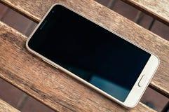Weißer Smartphone auf Holztischhintergrundbeschaffenheit mit Kopien-SP lizenzfreie stockfotos