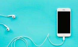 Weißer Smartphone, beweglich auf blauem Farbhintergrund Kommunikation lizenzfreies stockbild