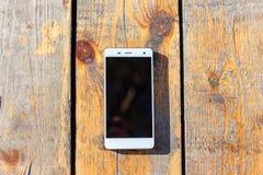 Weißer Smartphone, der auf einem Holztisch liegt stockbilder