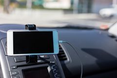 Weißer Smartphone im Halter schloss auf dem Schlag an, der leeres blac zeigt Stockfotos