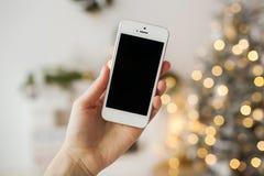 Weißer Smartphone mit dem Weihnachtsbaum im Hintergrund Stockfotografie