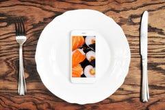 Weißer Smartphone mit Großleinwand auf der Platte mit Messer und für lizenzfreies stockfoto