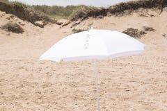 Weißer Sonnenschirm auf dem Strand Stockfotografie